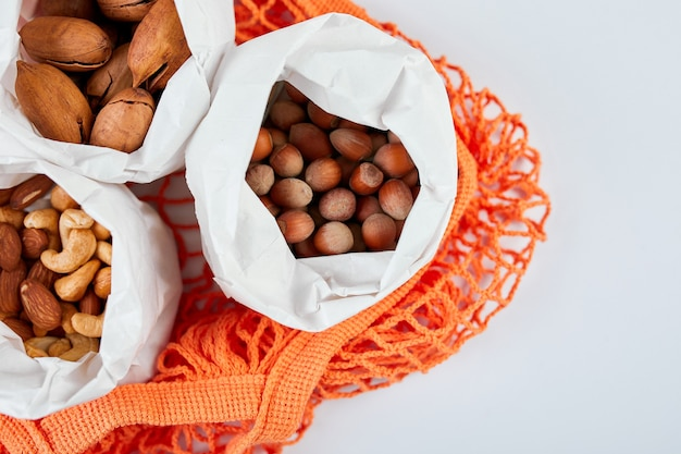 Diversos tipos de nueces sobre la mesa en bolsas en la bolsa de la compra sobre la superficie azul