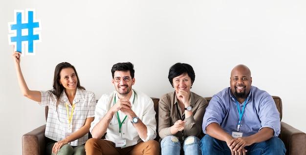 Diversos trabajadores sentados juntos mujer sosteniendo el icono de hashtag