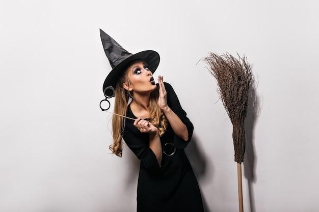Divertida chica caucásica posando en traje de bruja en carnaval. mujer de pelo largo con sombrero mágico de pie sobre una pared blanca con escoba.