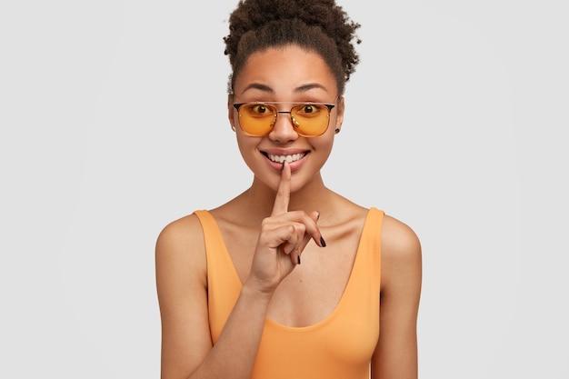 Divertida chica negra emocionada con cabello rizado, pide mantener en secreto, demuestra gesto de silencio