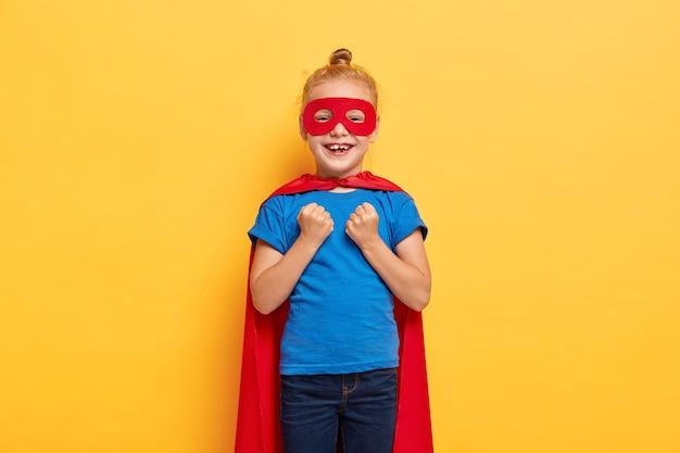 Divertida chica superheroína aprieta los puños