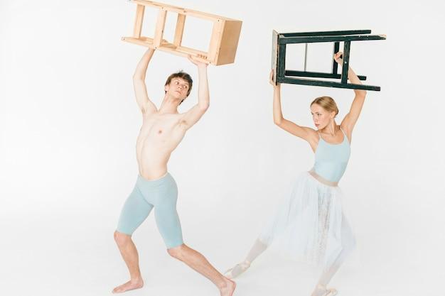 Divertida e inusual pareja de bailarines de ballet moderno posando con una silla en las manos sobre sus cabezas.