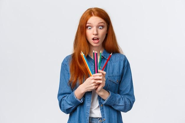 Divertida y emocionada, sorprendida linda pelirroja adolescente, chica astuta con camisa vaquera, mira fijamente los lápices de colores fascinada, tiene nuevo equipo para la clase de arte