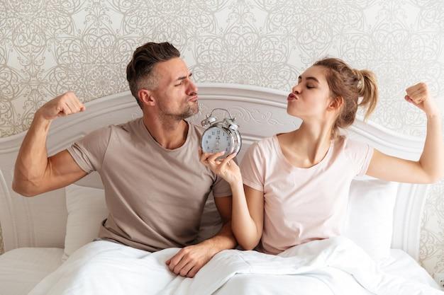 Divertida encantadora pareja sentados juntos en la cama con reloj despertador