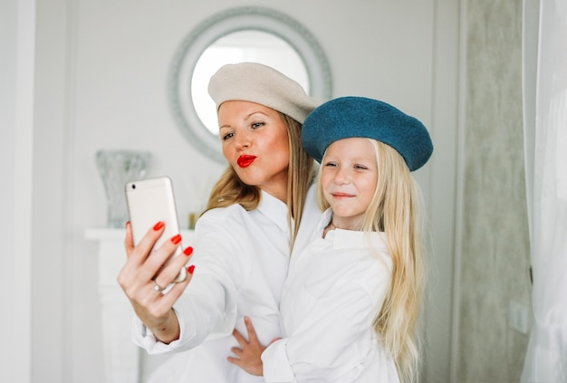 Divertida y feliz mamá de cabello largo y linda hija linda haciendo selfie juntos en el teléfono móvil en la sala de estar, estilo de vida familiar feliz