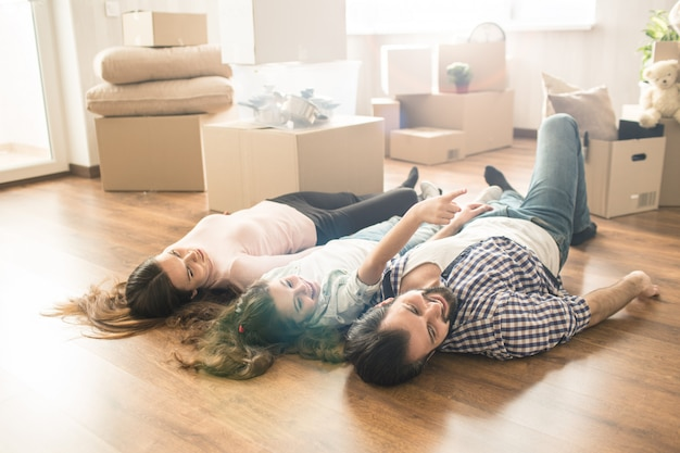 Divertida foto de familia tirada en el piso en su nuevo departamento. se divierten mucho juntos. también están buscando un lugar a la derecha.