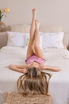 Divertida mujer acostada sobre la espalda con el pelo hacia abajo y las piernas hacia arriba