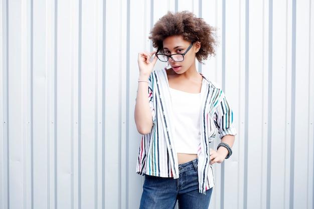 Divertida mujer afro negra feliz en camiseta blanca y jeans