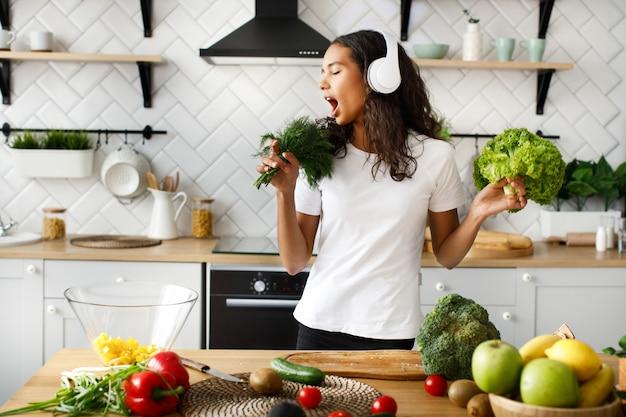 Divertida mujer mulata con grandes auriculares inalámbricos está cantando en un micrófono imaginario verde en la cocina moderna junto a la mesa llena de verduras y frutas