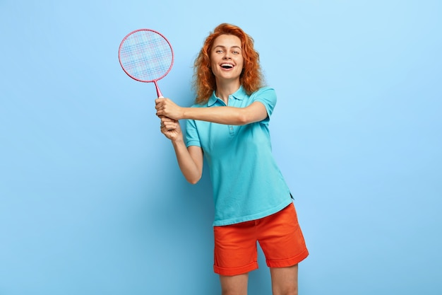 Divertida mujer pelirroja juguetona le gusta jugar al tenis, sostiene la raqueta