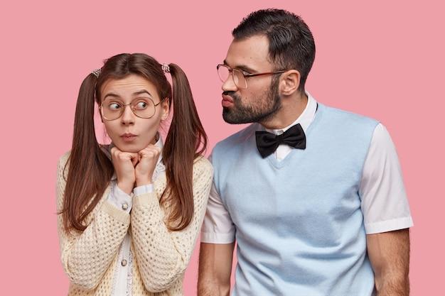 Divertida nerd femenina con dos colas de caballo, usa grandes gafas, va a recibir un beso de su novio, tiene la primera cita