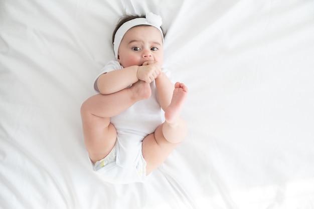 Divertida niña de 6 meses jugando con las piernas, acostado en la cama en su casa en ropa de cama blanca. vista superior.