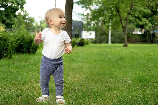 Divertida niña caucásica rubia más linda de 1 año de edad de pie sobre el césped
