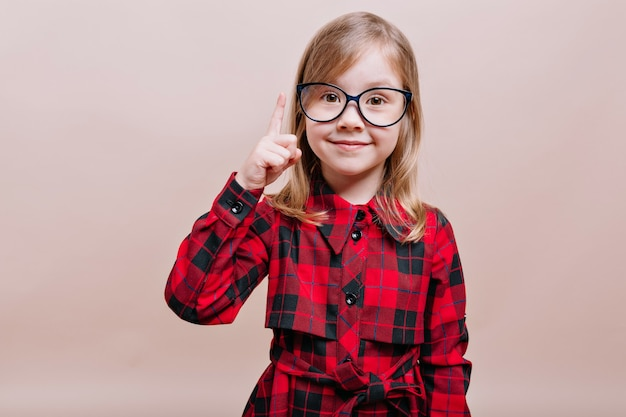 Divertida niña inteligente usa gafas y camisa a cuadros levantada con un dedo y sonríe al frente