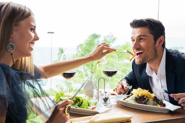 Divertida pareja almorzando en restaurante.