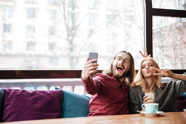 Divertida pareja amorosa sentada en la cafetería hace una selfie.