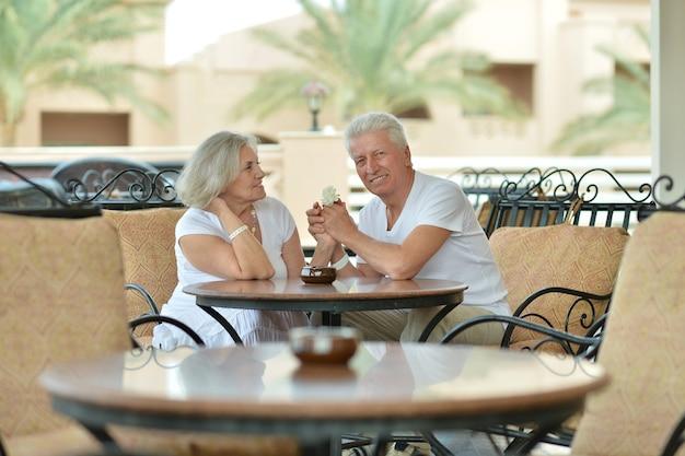 Divertida pareja de ancianos sonriente feliz en la mesa de café