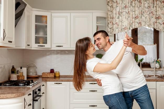 Divertida pareja bailando en la cocina