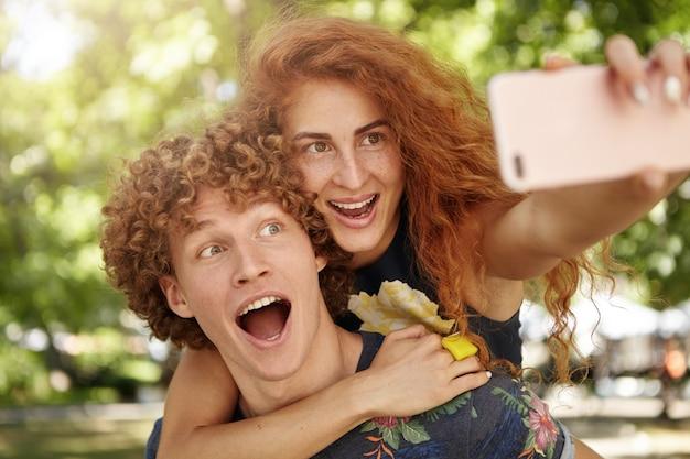 Divertida pareja de enamorados caminando en la calle posando para selfie
