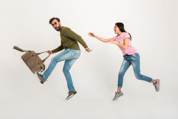 Divertida pareja feliz saltando mujer aislada, muy sonriente en camiseta rosa corriendo tras hombre en sudadera con bolsa de viaje, vestida con jeans