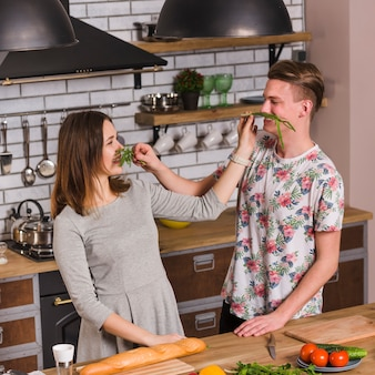 Divertida pareja haciendo bigote de verdes