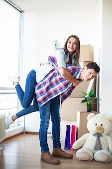 Divertida pareja joven disfruta y celebra mudarse a un nuevo hogar.