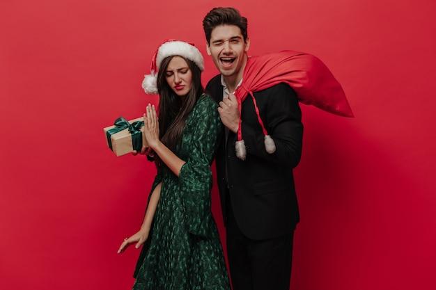 Divertida pareja de personas con trajes elegantes con atributos navideños posando emocionalmente aislado en la pared roja