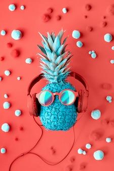 Divertida piña turquesa en gafas de sol y auriculares sobre papel rojo decorado