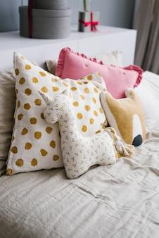 Divertidas almohadas hechas a mano, almohadas en forma de animales en la cama en el dormitorio