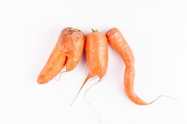 Divertidas y feas zanahorias vegetales, concepto de cero producción de residuos en la industria alimentaria