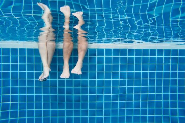 Divertidas piernas subacuáticas de la familia en poo de natación