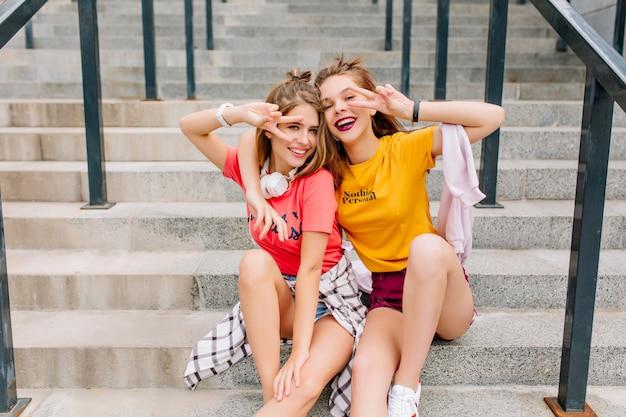 Divertidas señoritas inspiradas en traje de moda posando con gusto con el signo de la paz relajándose en escalones de piedra en día de verano