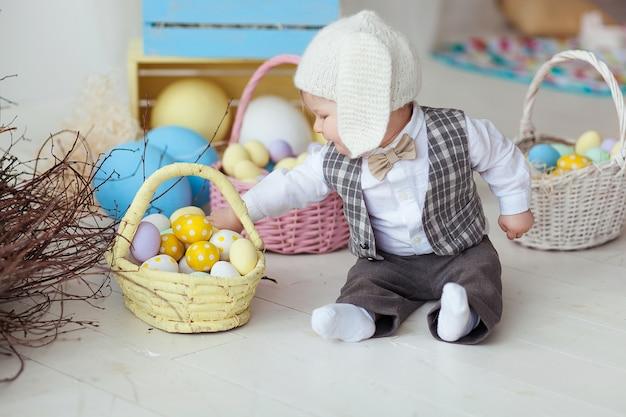 Divertido bebé feliz en el sombrero, corbata arco y traje jugando con huevos de pascua.