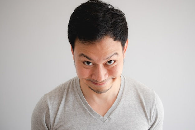 Divertido complicado torpe sonrisa cara de hombre en camiseta gris.