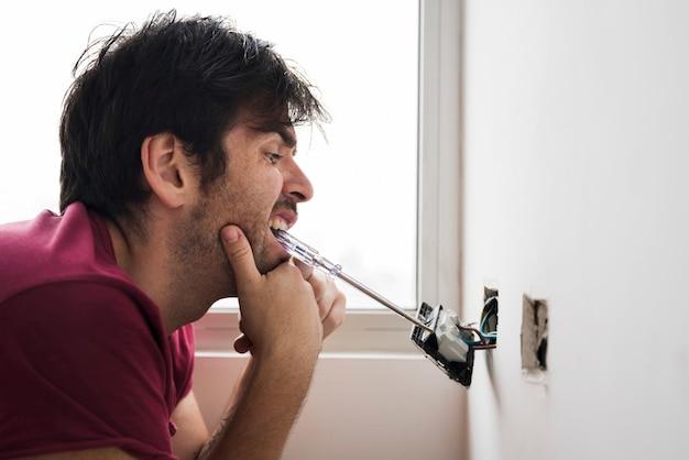 Divertido electricista instalando el enchufe con un destornillador en la boca