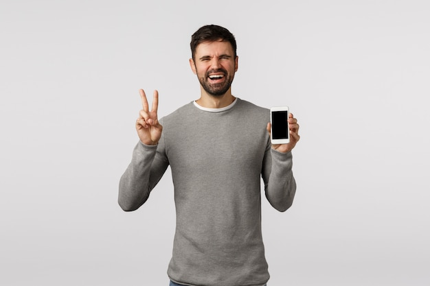 Divertido y emotivo, carismático hombre con barba que sostiene un teléfono inteligente, hace las paces, el signo de la victoria, muestra la pantalla del móvil como producto publicitario, sitio de compras o solicitud de seguimiento,