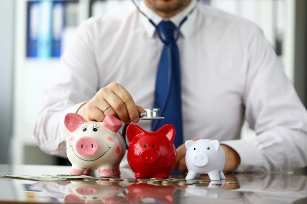 Divertido empresario escucha tres piggybanks por dinero en efectivo
