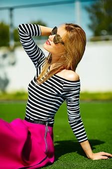 Divertido glamour loco elegante sexy sonriente hermosa rubia joven modelo en ropa hipster rosa sentada en el césped en el parque