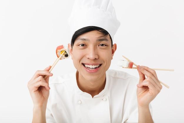 Divertido hombre jefe asiático en uniforme de cocinero blanco comiendo sushi con palillos aislados sobre la pared blanca