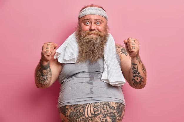 Divertido hombre con sobrepeso sudoroso después de cardio intensivo, levanta los puños cerrados, vestido con ropa deportiva, hace ejercicios matutinos para perder peso y pone todos los esfuerzos para estar en forma y saludable. deporte y obesidad