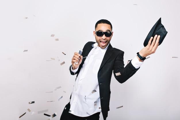 Divertido joven emocionado en traje con gran celebración de fiesta en oropel. usar gafas de sol negras, sonreír, cantar, escuchar música, expresar positividad.