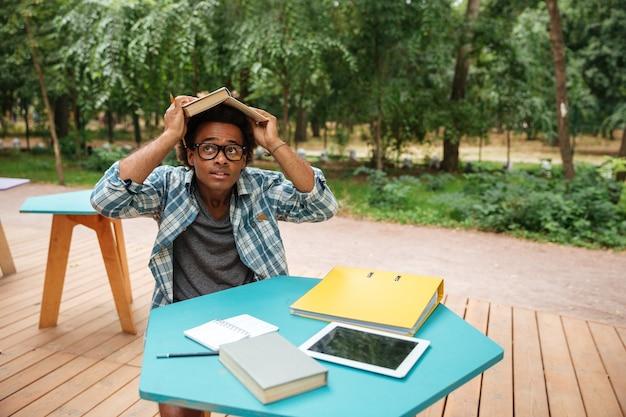 Divertido joven juguetón con libro en la cabeza sentado en la cafetería al aire libre