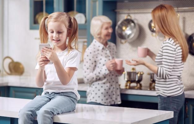 Divertido juego. adorable niña sentada en la encimera de la cocina y jugando con su teléfono mientras su madre y su abuela charlan y beben café en el fondo