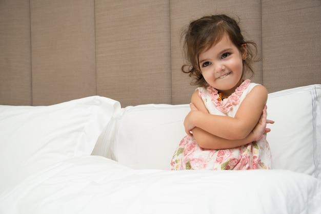 Divertido niña abrazándose a sí mismo en la cama
