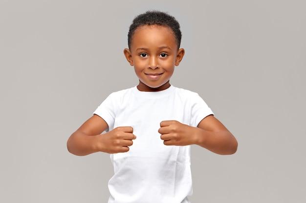 Divertido niño africano de diez años en camiseta blanca manteniendo los puños cerrados frente a él demostrando fuerza o sosteniendo objetos invisibles