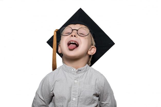 Divertido niño rubio con grandes gafas y un sombrero académico muestra lengua.