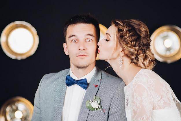 Divertido novio con los ojos bien abiertos está siendo besado por su bella novia con peinado trenzado