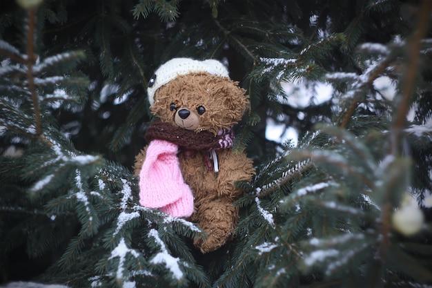 Divertido oso de peluche marrón vestido con gorro de punto y bufanda en ramas de abeto cubierto de nieve al aire libre en invierno