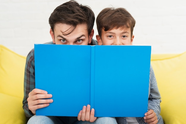 Divertido padre e hijo cubriendo sus rostros