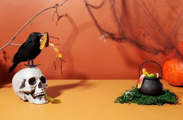 Divertido paisaje de halloween. cráneo y cuervo negro con gusano de gelatina, caldero de bruja negro lleno de serpientes de gelatina en musgo verde